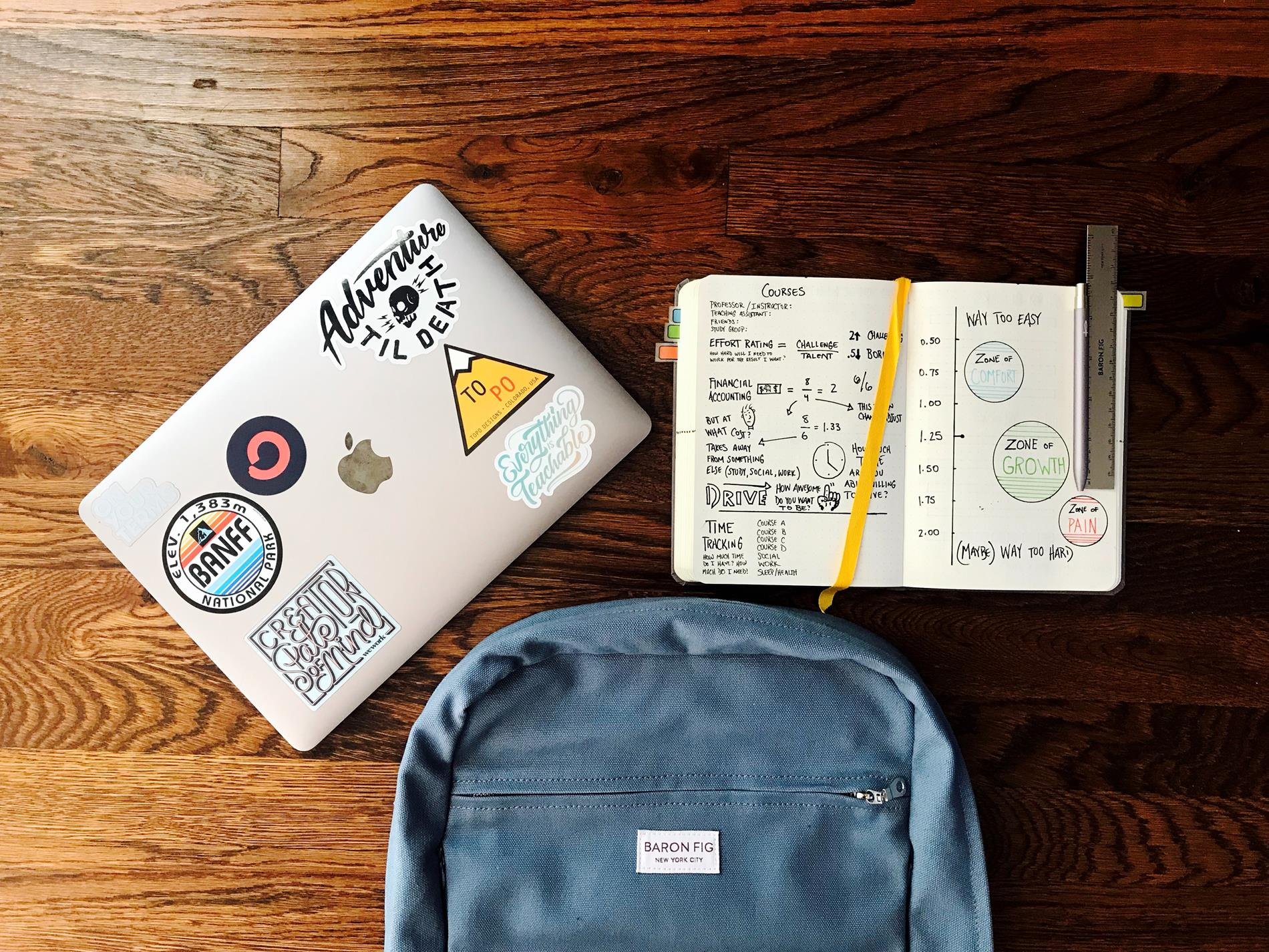 overhead image of mac laptop with stickers, open notebook with school notes, and blue backpack