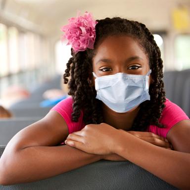 Girl wearing mask on school bus.