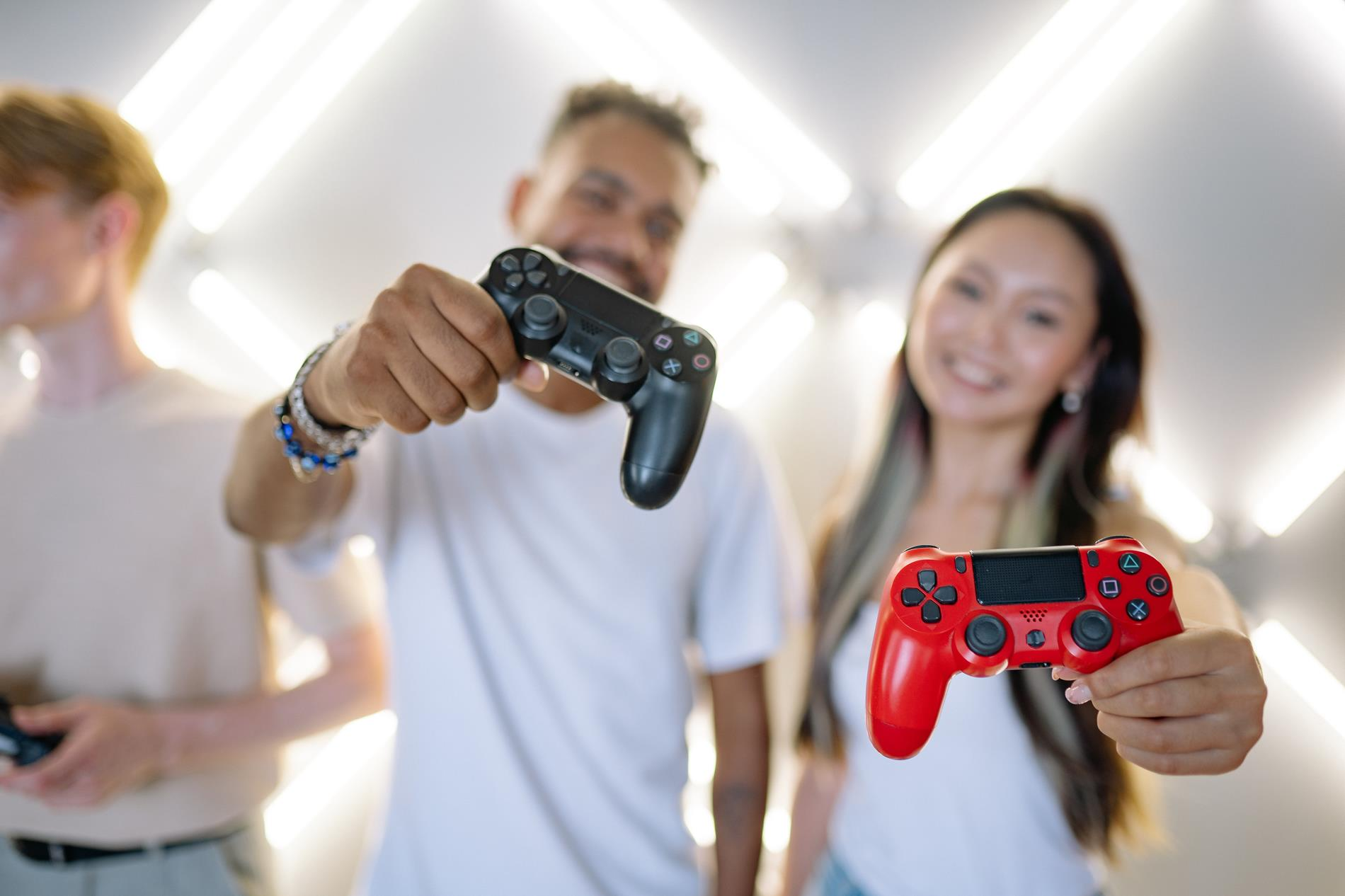 A male and female student stand in the background, blurred, holding playstation controllers out in front of themselves towards the camera